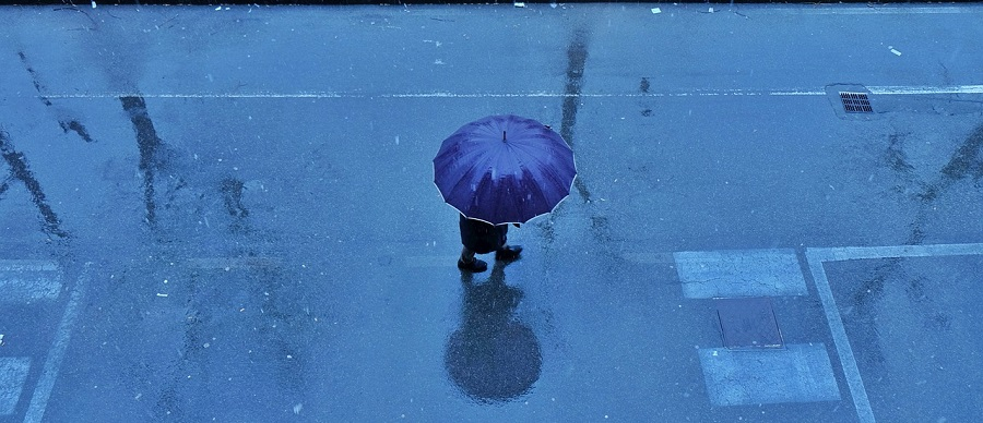 Financial protection, blue umbrella in rain
